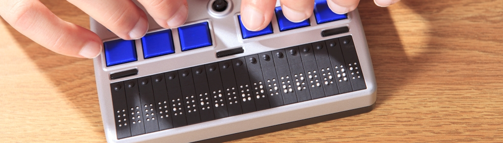 Student with visual impairment using her Braille display to communicate